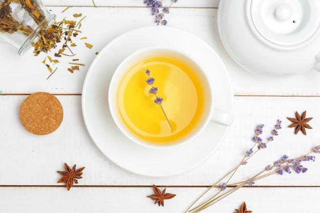 Teekanne und tassen tee auf einem weißen hölzernen hintergrund Premium Fotos