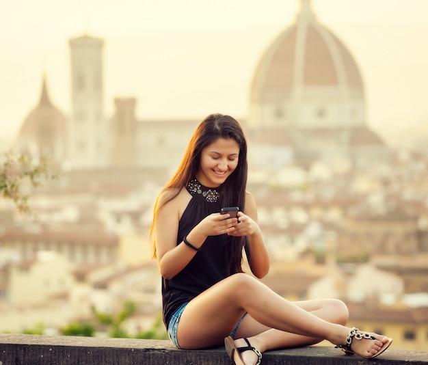 Teen bei sonnenuntergang in florenz nutzt das smartphone Premium Fotos