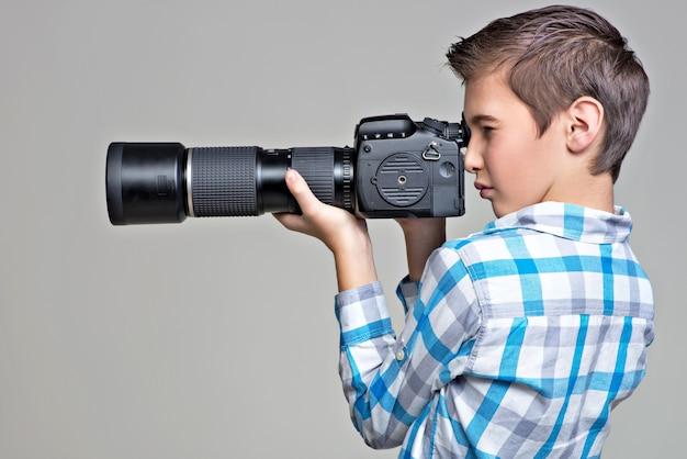 Teen boy mit dslr-kamera fotografieren. junge mit kamera, die bilder macht. profilporträt. Kostenlose Fotos