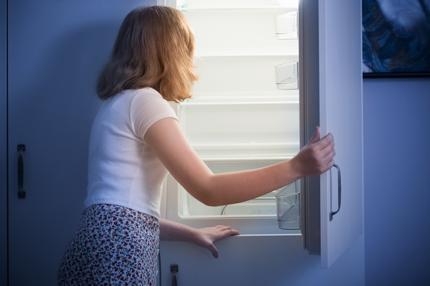 Teen girl am leeren kühlschrank Premium Fotos