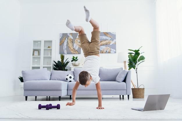 Teen junge, der hände stehende übungen am gemütlichen wohnzimmer tut. Premium Fotos