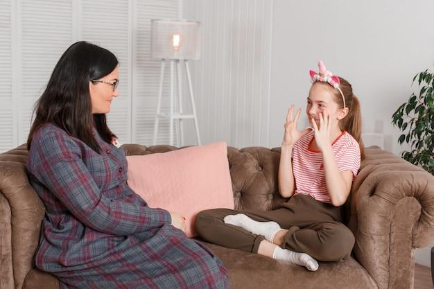 Teen mädchen an der rezeption beim psychotherapeuten. psychotherapie für kinder. der psychologe arbeitet mit dem patienten. lächelndes sitzen des mädchens auf einem sofa nahe bei einem sitzenden ärztintherapeuten Premium Fotos