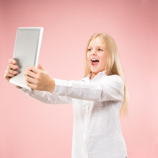 Teen mädchen mit laptop. liebe zum computerkonzept. attraktives weibliches porträt in halber länge vorne, trendiges rosa hintergrundbild Kostenlose Fotos