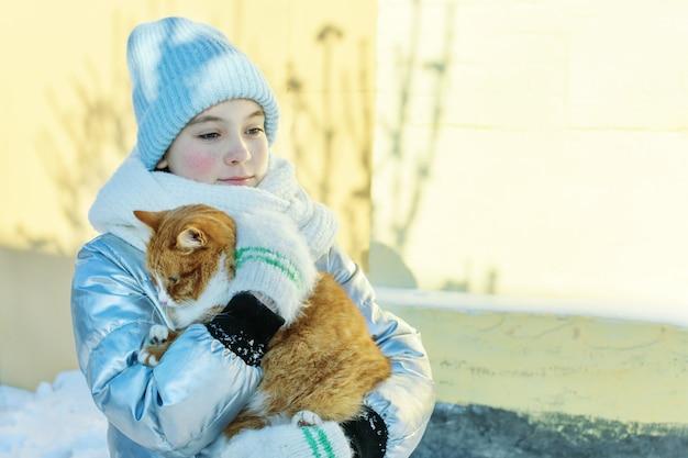Teen mädchen trägt obdachlose katze in ihren händen am wintertag. pflege streunender tiere. Premium Fotos