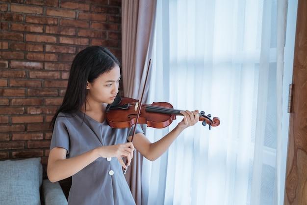 Teenager, der lernt, ein geigeninstrument zu spielen Premium Fotos