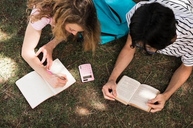 Teenager, der mit buch und notizblock auf gras liest Kostenlose Fotos
