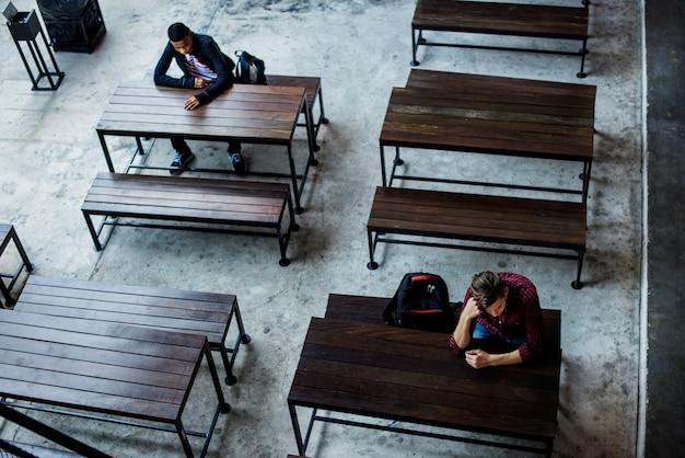 Teenager, die allein in einer leeren kantine sitzen Kostenlose Fotos