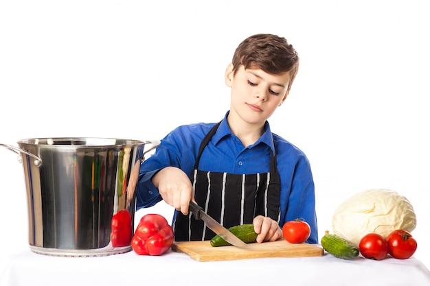 Teenager im kochchefhut und -schutzblech fügt salatschüssel auf dem schneidebrett, das durch das lokalisierte gemüse und gewürzen umgeben wird, würze hinzu Premium Fotos