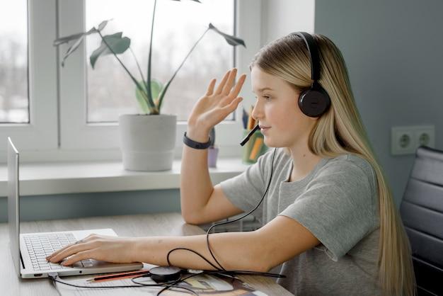 Teenager im kopfhörer hebt ihre hand, während sie online-unterricht zu hause hat Premium Fotos