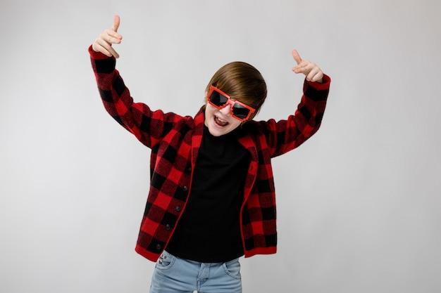 Teenager in der modernen kleidung und in der sonnenbrille Premium Fotos