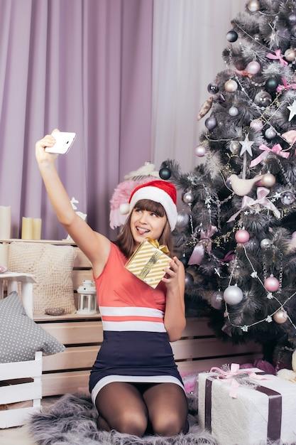 Teenager macht ein selfie mit einem goldenen weihnachtsgeschenk inmitten festlicher neujahrsdekorationen der rosa farbe. Premium Fotos