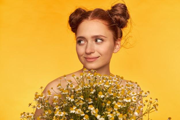 Teenager-mädchen, glücklich aussehende rote haarfrau mit zwei brötchen. frisur. halten sie einen strauß wildblumen in der hand, lächeln sie und beobachten sie links den kopierbereich über der gelben wand. nahansicht Kostenlose Fotos