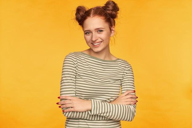 Teenager-mädchen, glücklich aussehende rote haarfrau mit zwei brötchen. trägt einen gestreiften pullover und hält die hände auf einer brust gekreuzt. lächelnde beobachtung isoliert über gelber wand Kostenlose Fotos