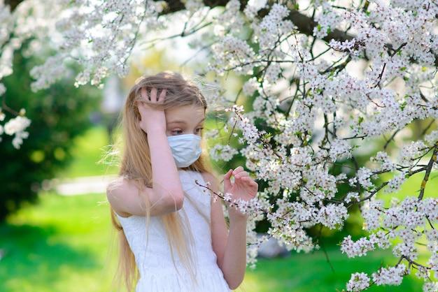 Teenager-mädchen in der medizinischen maske im blühenden garten des frühlings. konzept der sozialen distanz und prävention von coronavirus. Premium Fotos
