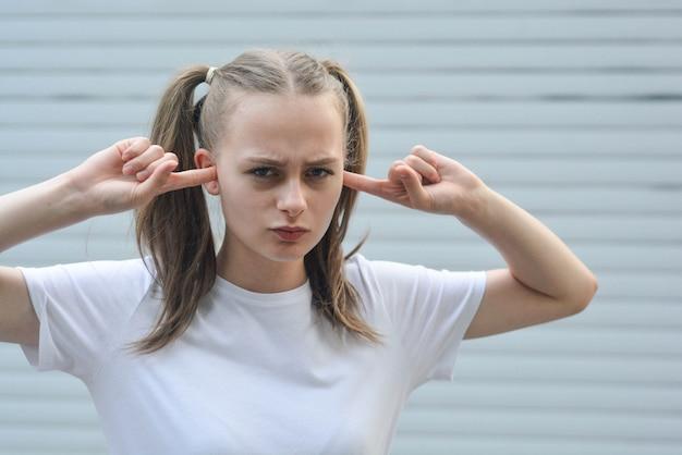 Teenager-mädchen mit den fingern in den ohren Premium Fotos
