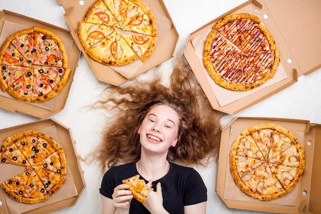 Teenager-mädchen mit einem stück pizza in den händen und pizzaschachteln um ihre lügen Premium Fotos