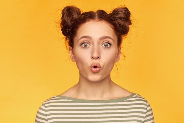 Teenager-mädchen, schockiert aussehende rote haarfrau mit zwei brötchen. versuche die kerzen auszublasen. tragen eines gestreiften pullovers und beobachten isoliert, nahaufnahme über gelber wand Kostenlose Fotos