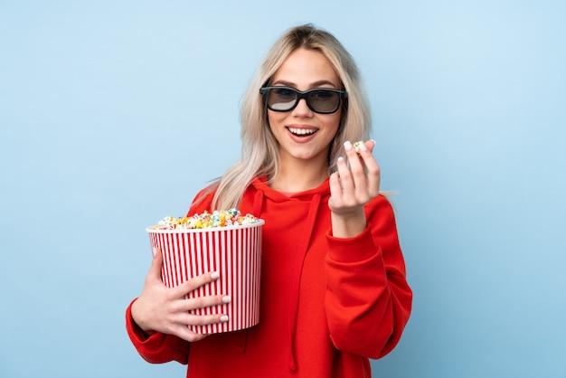 Teenager-mädchen über blaue wand mit 3d-brille und hält einen großen eimer popcorn Premium Fotos