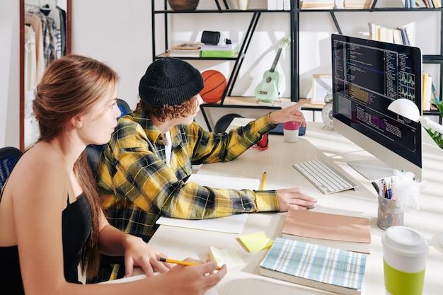 Teenager und mädchen arbeiten gemeinsam an hausaufgaben für den informatikunterricht und suchen nach fehlern im programmiercode Premium Fotos