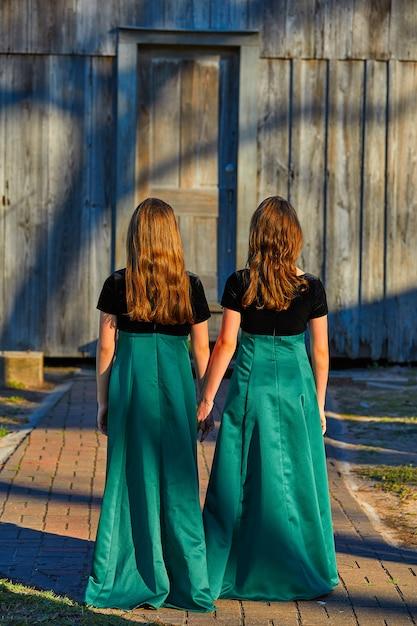Teenie-schwestern des langen kleidzwillings hand in hand Premium Fotos