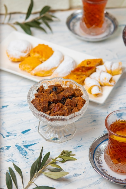 Teeservice mit verschiedenen traditionellen nüssen, zitronen, konfitüren und süßigkeiten auf weißer tischdecke Kostenlose Fotos