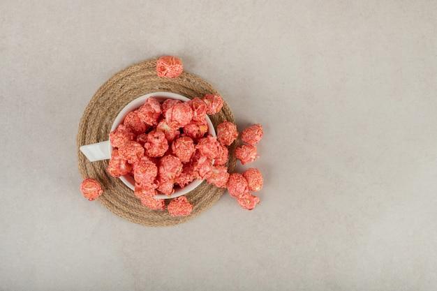 Teetasse auf einem untersetzer über fließend mit rotem popcorn auf marmor. Kostenlose Fotos