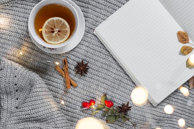Teetasse auf gestricktem tuch mit notizblock Kostenlose Fotos