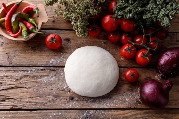 Teigklumpen auf einem holztisch, umgeben von tomaten, pfeffer und zwiebeln Kostenlose Fotos