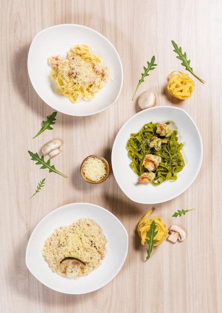 Teigwaren in den weißen platten mit verschiedenen bestandteilen auf hellem holztisch in einem restaurant. Premium Fotos