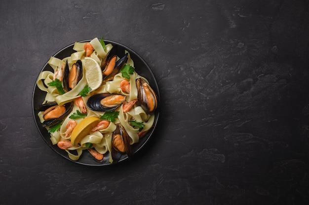 Teigwaren mit meeresfrüchten auf steintabelle. muscheln und garnelen. draufsicht mit textfreiraum. Premium Fotos