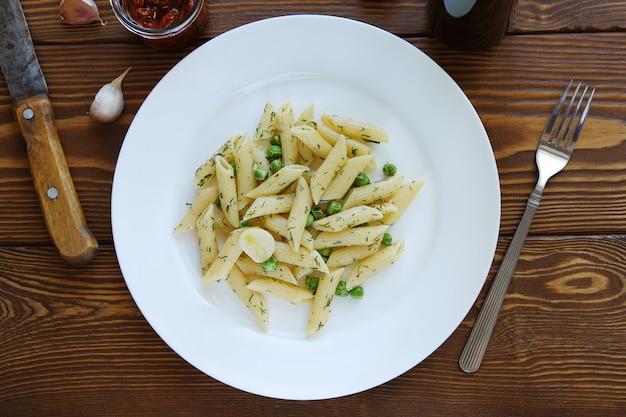Teigwaren mit pestosoße, grünen erbsen, knoblauch und dill auf einer platte auf einem holztisch. italienische küche. Premium Fotos