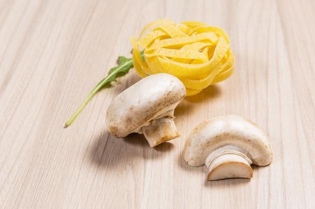 Teigwaren mit pilzen und arugula auf holztisch im restaurant. zutaten auf holzrücken Premium Fotos