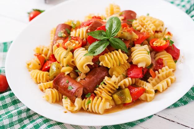 Teigwaren mit tomatensauce mit wurst, tomaten, grüner basilikum verziert in der weißen platte auf einem holztisch. Kostenlose Fotos