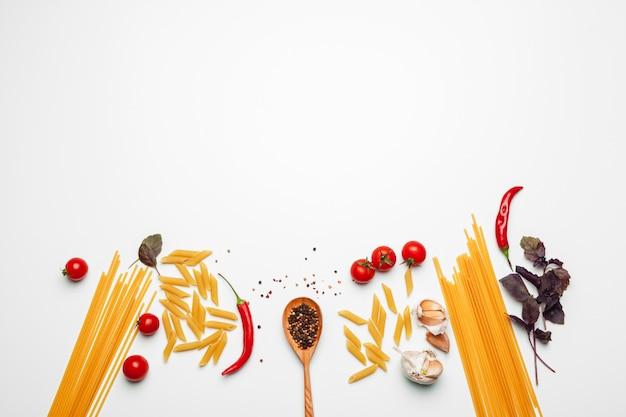 Teigwaren-spaghettis mit bestandteilen für das kochen von teigwaren auf einem weißen hintergrund, draufsicht. Premium Fotos