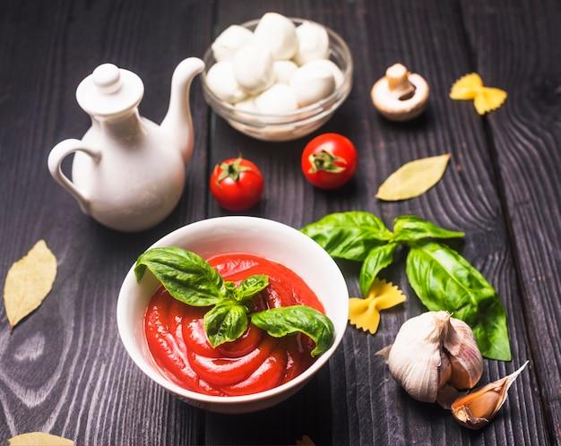 Teigwaren- und tomatensauce farfalle mit bestandteilen auf holztisch Kostenlose Fotos
