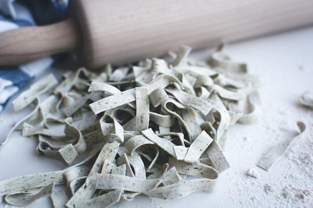 Teigwarenbandnudeln bedeckt durch mehl mit einer hölzernen rolle auf einem weißen hintergrund Kostenlose Fotos