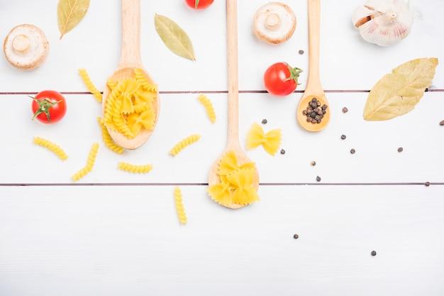 Teigwarenbestandteile mit gewürzen und gemüse auf weißer plankentabelle Kostenlose Fotos