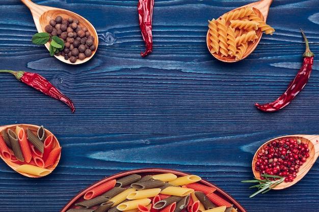 Teigwarenspaghettis, gemüse und gewürze, auf holztisch Premium Fotos