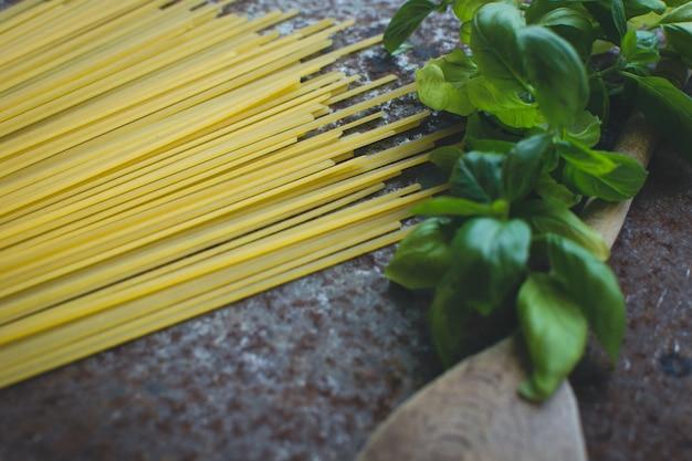 Teigwarenspaghettis mit basilikum und hölzernem löffel auf einem rostigen metallischen hintergrund Kostenlose Fotos