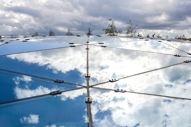 Teil der glaskonstruktion, die den blauen himmel reflektiert. Premium Fotos