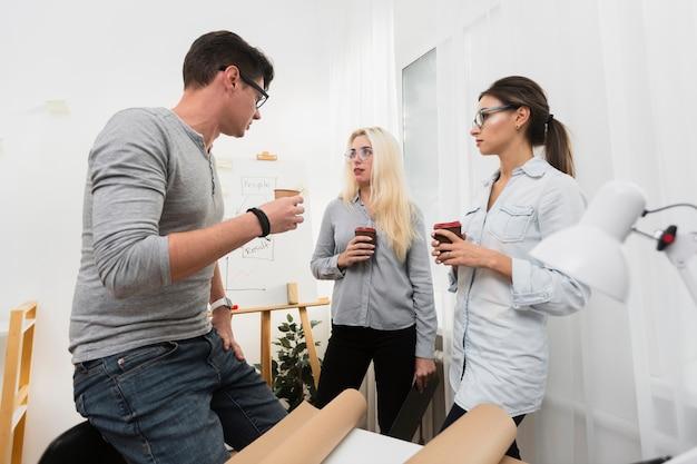 Teilhaber, die tasse kaffees halten und einander betrachten Kostenlose Fotos