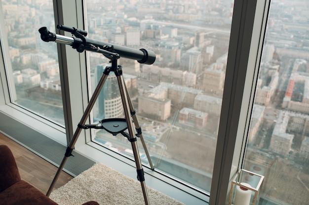 Teleskop am fenster des wolkenkratzers Premium Fotos