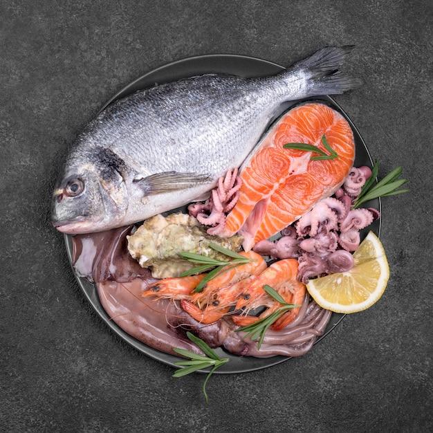 Teller gefüllt mit frischem ungekochtem fisch mit meeresfrüchten Premium Fotos