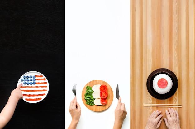 Teller mit essen in form von flaggen von amerika, italien und japan. Premium Fotos