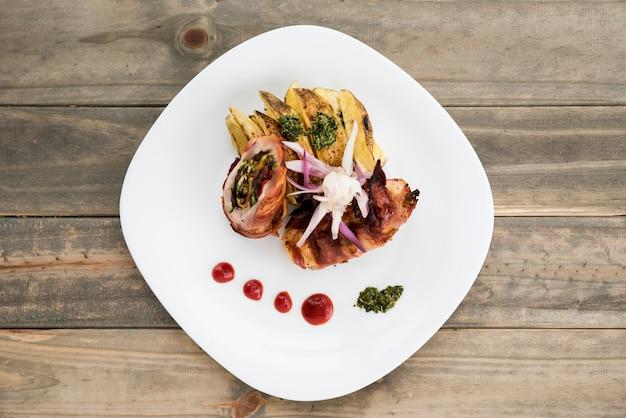 Teller mit fleisch und kartoffel auf hölzernem schreibtisch Kostenlose Fotos