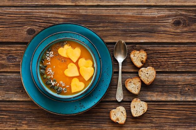Teller mit frischer hausgemachter kürbiscremesuppe mit samen und toast mit herzform Premium Fotos