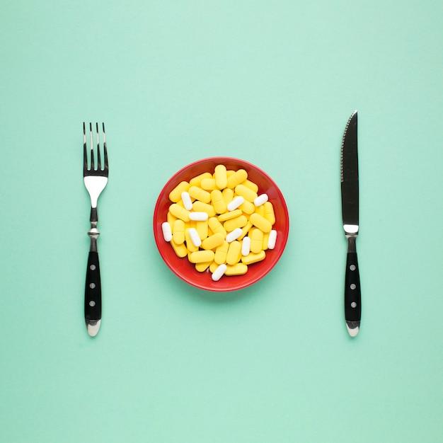 Teller mit gelben und weißen pillen mit besteck auf grünem hintergrund Kostenlose Fotos