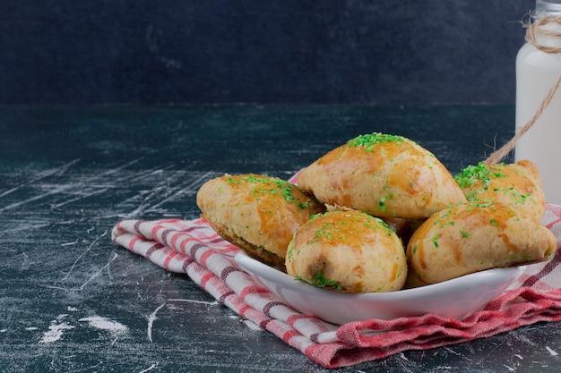 Teller mit hausgemachten keksen und glas milch auf marmortisch. Kostenlose Fotos