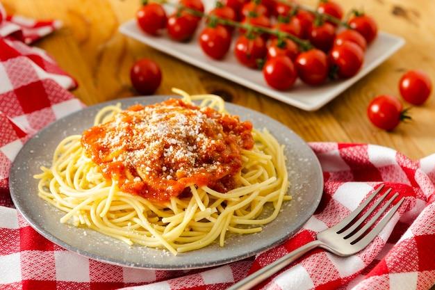 Teller mit nudeln mit tomaten auf tischdecke Premium Fotos
