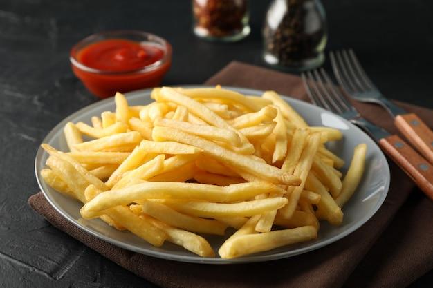 Teller mit pommes frites, serviette, roter sauce, gabeln auf schwarz. nahansicht Premium Fotos